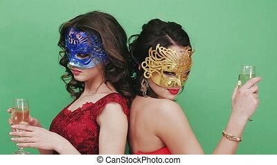 Two young girls in sexual Venetian masks. Studio green...