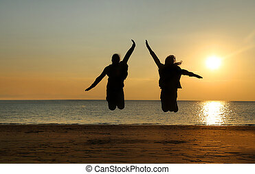 Two young girls jumping at beach