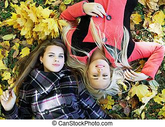 girls lie on the grass