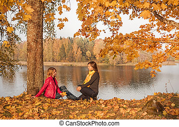 Two young girls on the lake in the evening rays of the autumn sun