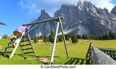 two young girls playing on playground and swinging on a...