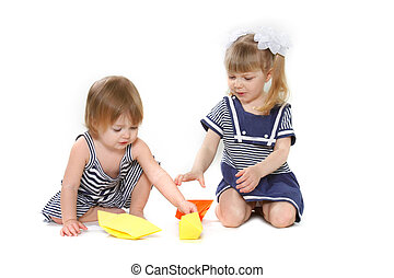 two young girls playing with paper ships over white