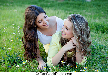 Two young girls resting on the grass.