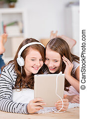Two young girls share headphones to listen music - Close-up...