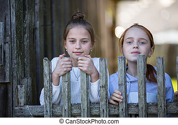 Two young girls sisters outdoors. Portraits.