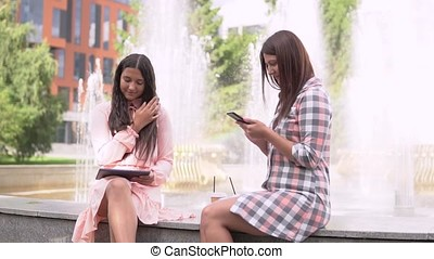 Two young girls sitting in a park near a fountain using a...