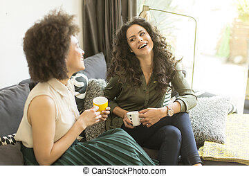 Two young girls sitting on the sofa in the room, drinking coffee and talking