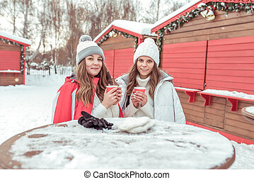 Two young girls students girlfriends. In winter, they hold cups coffee and tea on street in their hands. Keep warm in cold weather. Breakfast and lunch at winter resort. Women communicate and smile.