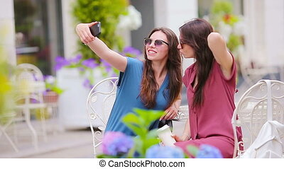 Two young girls taking selfie by smart phone at the outdoors cafe.