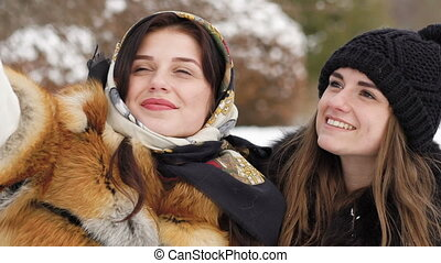 Two young girls taking selfie in winter park. Slow motion