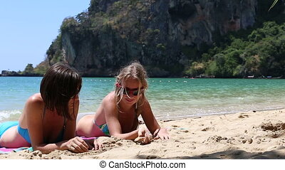 two young girls tan talk  on beach against cliff