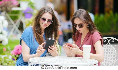 Two young girls using smart phone at the outdoors cafe. Two women after shopping with bags sitting in openair cafe with coffee and using smartphone