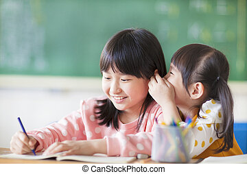 Two young girls whispering and sharing a secret