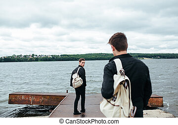 two young guys standing on a pier