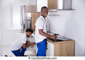 Two Young Handy Men Fixing The Equipment In The Kitchen