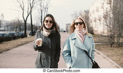 Two young happy Caucasian ladies walking together. Girlfriends chatting in the street. Business women meeting outside.