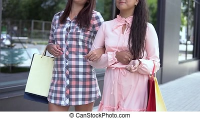 Two young happy girls go after shopping holding packages with purchases. slow motion.