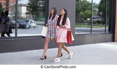 Two young happy girls go after shopping near the shopping center holding shopping bags. slow motion. HD
