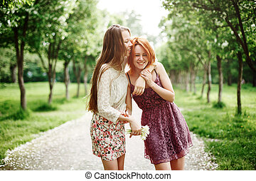 Two Young Happy Girls Having Fun in the Park