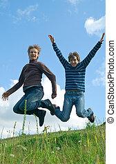men jumping against summer landscape
