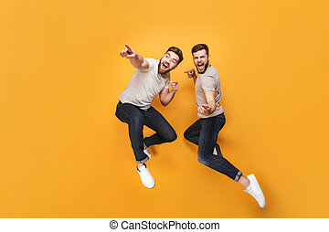 Two young happy men jumping together