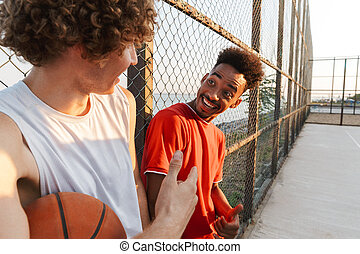 Two young happy multiethnic men basketball players standing ...