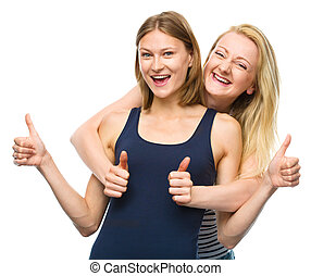 Two young happy women showing thumb up sign