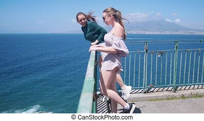 Two young happy women standing on an observation deck and...