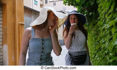 Two young happy women walking in panamas on the streets...