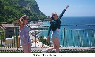 Two young happy women walking on an observation deck on a...