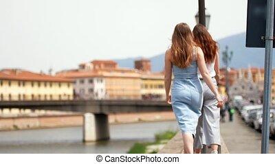 Two young happy women walking on the promenade of italian...