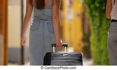 Two young happy women with baggage going to the alley of...