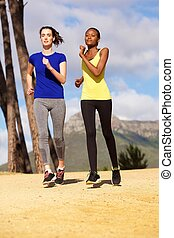 Two young healthy women jogging together outdoors