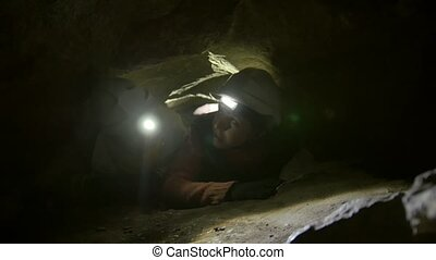 Two young hikers explorers stuck in the narrow hole in dark...
