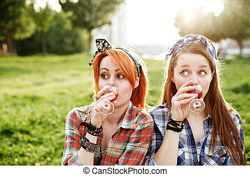 Two young hipster girls having fun on the picnic