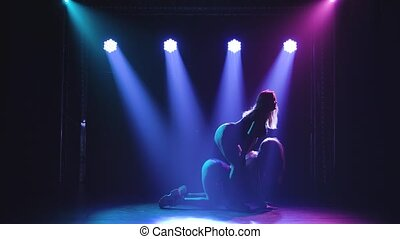 Two young hot women sexually move their body and ass. Twerk in a duet against the background of spotlights. Slow motion
