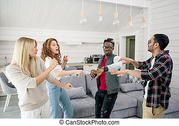 Two young intercultural couples enjoying dancing together in living-room