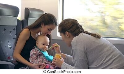 Two Young Ladies Feeding a Baby on the Train