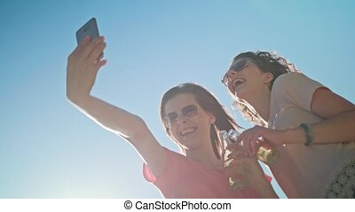 Two Young Ladies Making a Selfie on the Beach