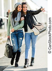 Two young ladies walking and shopping happily pointing in a direction