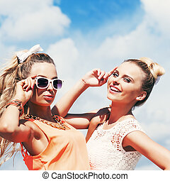 two young lady in summer apparel pose for the camera