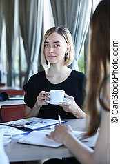 two young lady talk sit at table in cafe