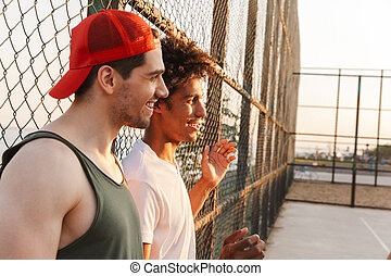 Two young laughing multiethnic men basketball players