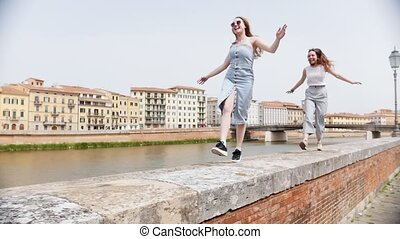 Two young laughing women walking and jumping along the curb...
