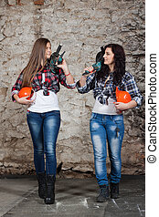 Two young long-haired woman with a drill