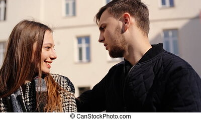 Two young lovers talking to each others while sitting on a bench at the street.