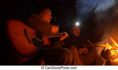 Two young male friends by the bonfire into the night forest singing songs by the guitar