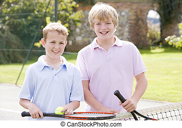 Two young male friends with rackets on tennis court smiling