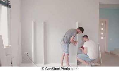 Two young man do the repairs in the bright apartment. Men assemble furniture together.