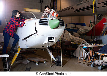 Two young mechanics, man and woman, repairing light sport plane in workshop